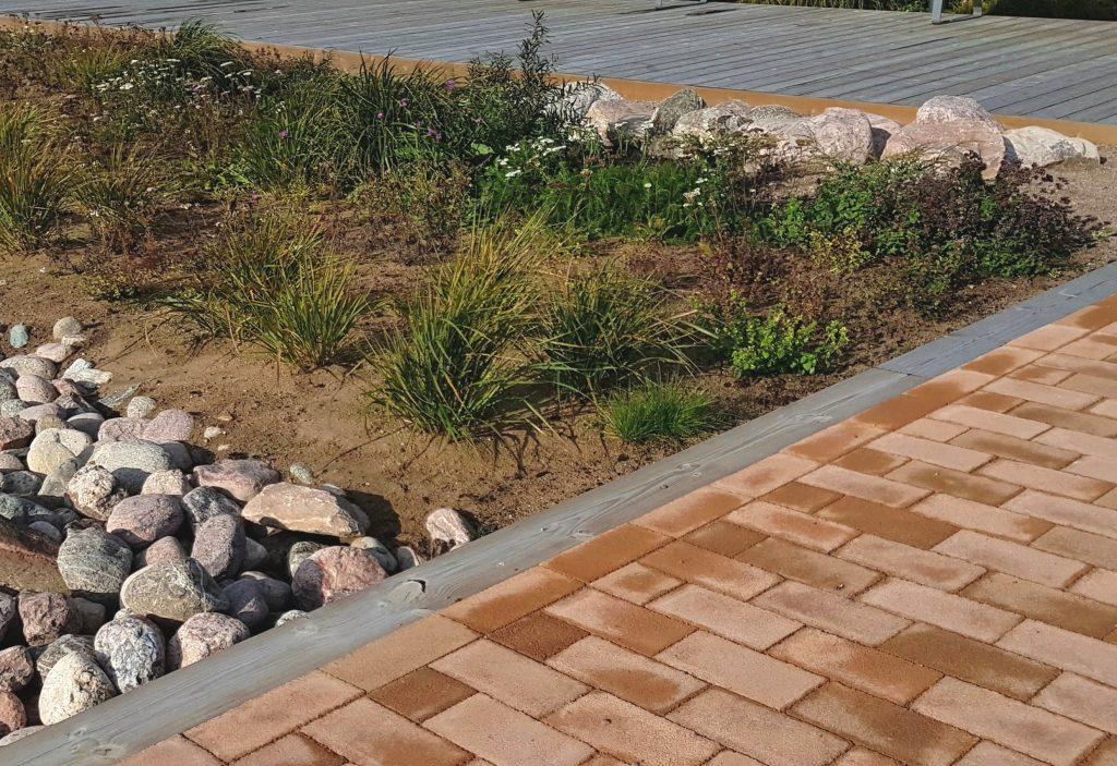 Pintamateriaaleja: kestopuu, betonikiveys ja luonnonkiviä